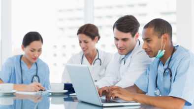 A group of doctors sit at a table, coming up with HIPAA compliant medical tech solutions.