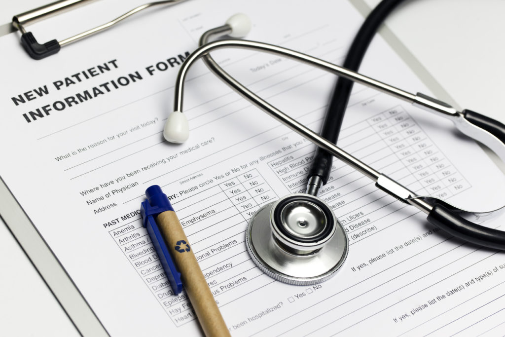 """A clipboard with a form reading """"New Patient Information"""" with a stethoscope and a pen, representing the cost to acquire a new patient lead."""