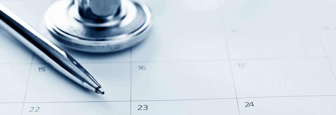 A stethoscope and a pen resting on a conventional paper calendar, to show how appointments were scheduled before online appointment booking.