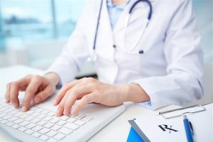 A doctor reviews their website on a laptop that is designed for practical usefulness.