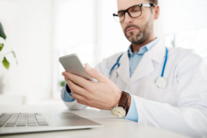 A doctor makes a post for his social media strategy and checks to assure that it doesn't violate any HIPPA regulations.