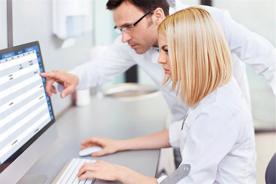 Two medical professionals analyze their local competition at a computer which is a critical step for new patient acquisition.