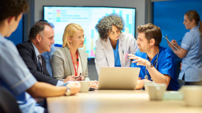 A group of healthcare professionals meet and discuss how to keep their digital advertising costs down by analyzing the various resources available.